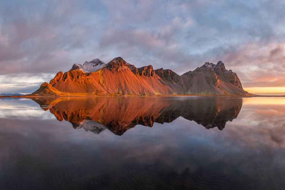 Reflection of Vestrahorn mountain in Iceland at colorful sunrise